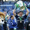 Shane Horgan raises the Heineken Cup trophy high in celebration as Leo the Lion waits his turn