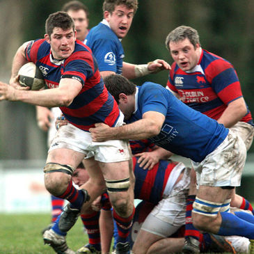 Clontarf flanker Simon Crawford is tackled by Colm McMahon of St. Mary's