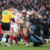 Ulster's recently-announced Lion Stephen Ferris tries to power out of a tackle from Deiniol Jones