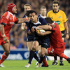 French referee Jerome Garces looks on as Isa Nacewa is sandwiched by the Munster defence