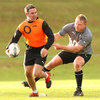 Tom Court has a grasp of a training bib as he holds back his Ulster colleague Paddy Wallace