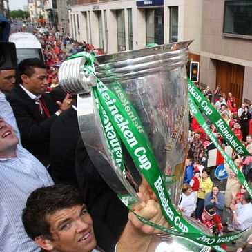 Donncha O'Callaghan lifts the trophy as Munster's open top bus moves through Limerick