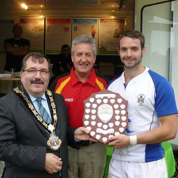 Dungannon captain Chris Henderson receives the Will Totten trophy from the Mayor of Newtownabbey