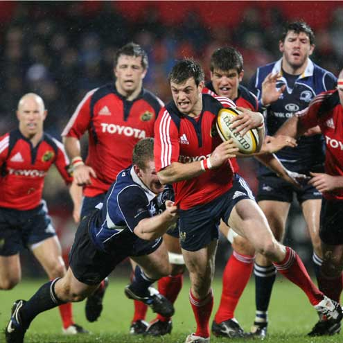 Munster's Ian Dowling is tackled by Leinster back rower Stephen Keogh