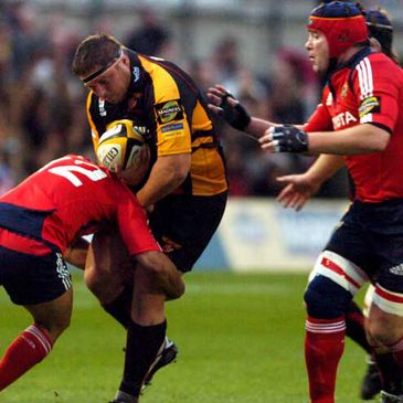 Rhys Thomas of the Dragons is tackled by Munster centre Lifeimi Mafi