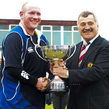 Leinster's Eoin Collins accepts the trophy from Ulster Branch President David Workman